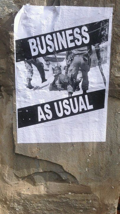"The photo that is posted on the street is from September 28th, 2016 when the University Currently Known as Rhodes(UCKAR) allowed South African police officials to  drag, threaten, and shoot at students who were fighting for free, quality, decolonized education. Since that date, this photo has circulated alongside many others. The purpose of the words ""BUSINESS AS USUAL"" on this image is to critique my host universities lack of making any strides towards supporting students in their fight towards free, quality, decolonised education."